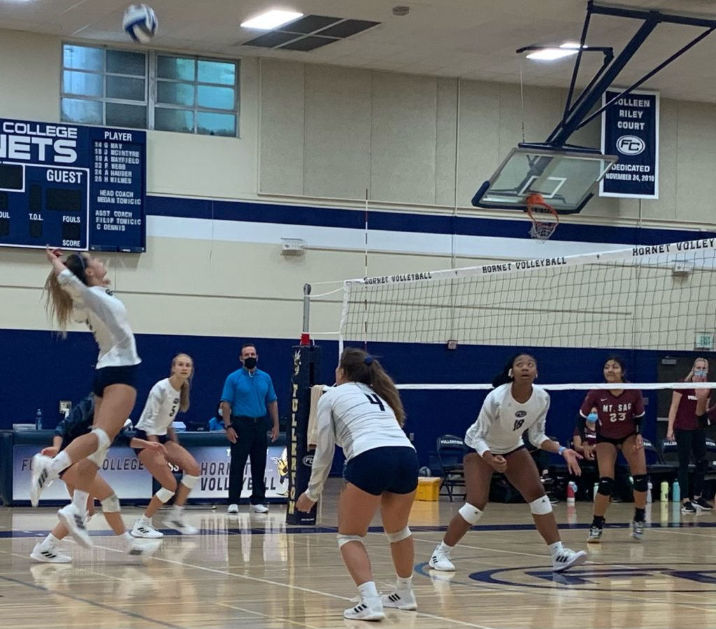 Sophomore Faith Webb goes to spike the ball set up by teammate Mckenna Mokry(left of Webb). While Nya Veikos and Jade McIntyre(right side, forward right) anticipate the move. Photo credit: Corinna Ortega