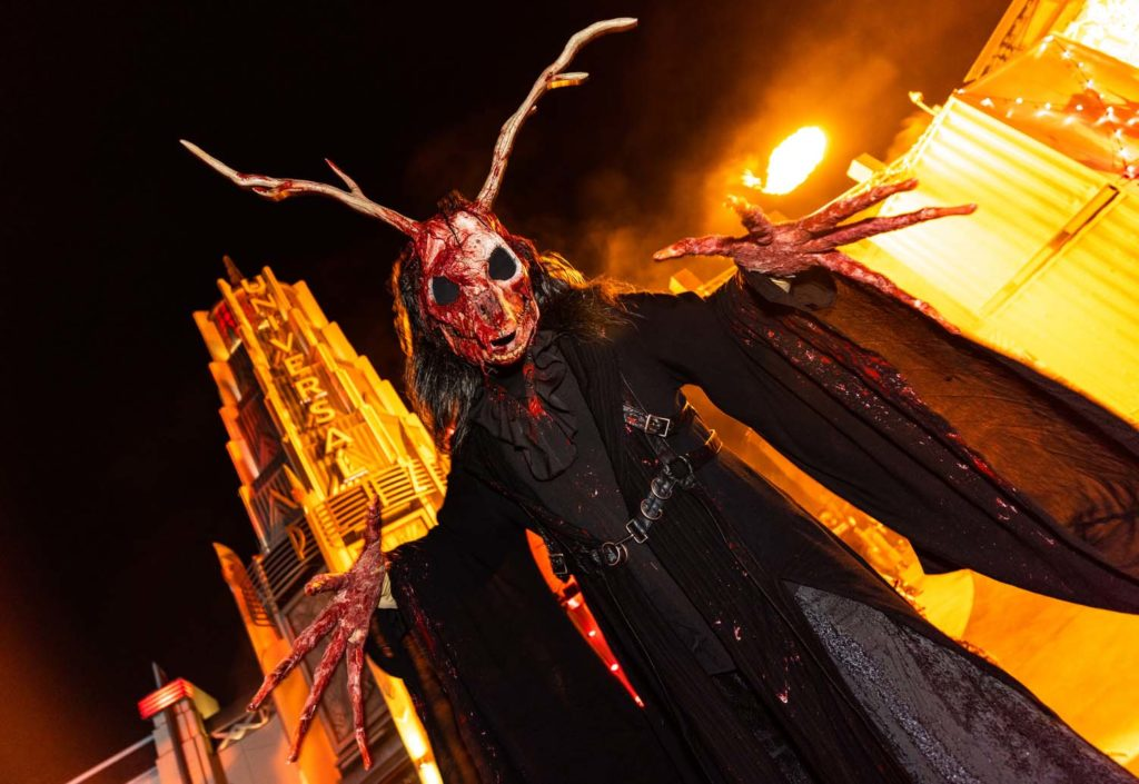 A bloody demon on stilts welcomes visitors to Demon City scare zone.