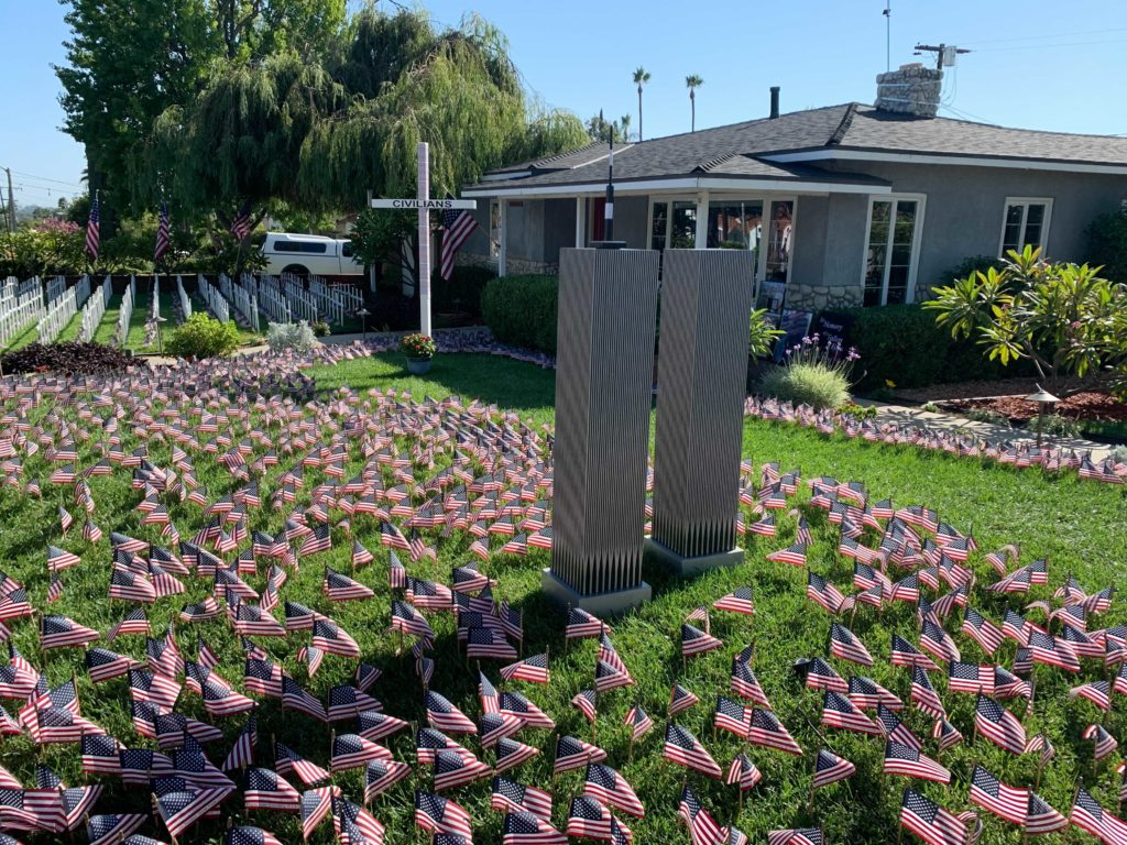 A model of the World Trade Center lies to one side of the memorial to notate those who died within.