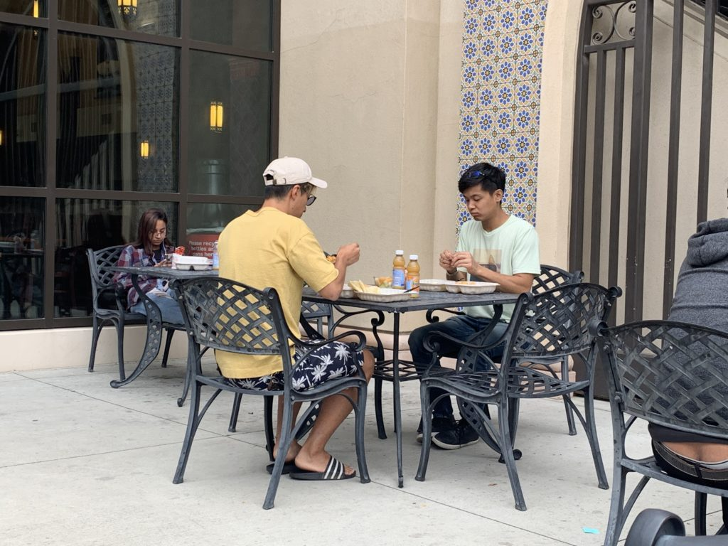 Fullerton College students eating free breakfast in the outside patio area of the 200 building from the grab-and-go meal program.