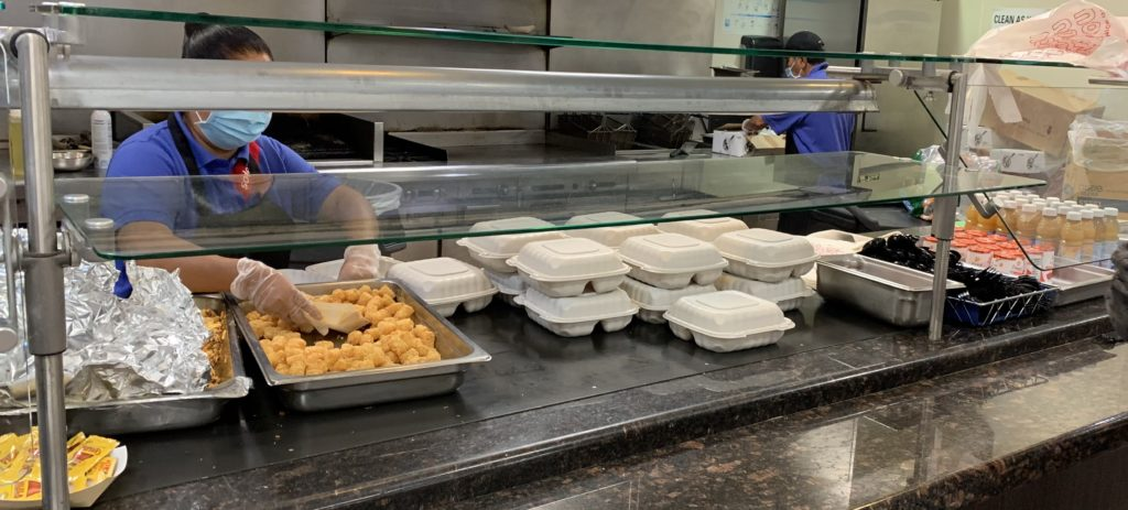 Sudexo employees contracted by Fullerton College prepare hot meals for students in to-go boxes, serving chorizo and eggs, tater tots, yogurt, fruit cups, and fruit juice.